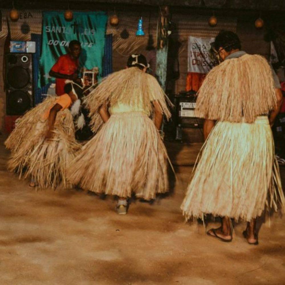 Brincantes de reisado: três pessoas vestidas de palha.