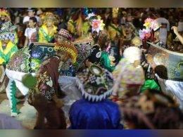 Um boneco de Bumba meu Boi está dançando em uma apresentação. Ele está todo enfeitado com brilhos, e desenhos de flores. Ao redor do boi há várias pessoas dançando com chapeis também enfeitados e coloridos.