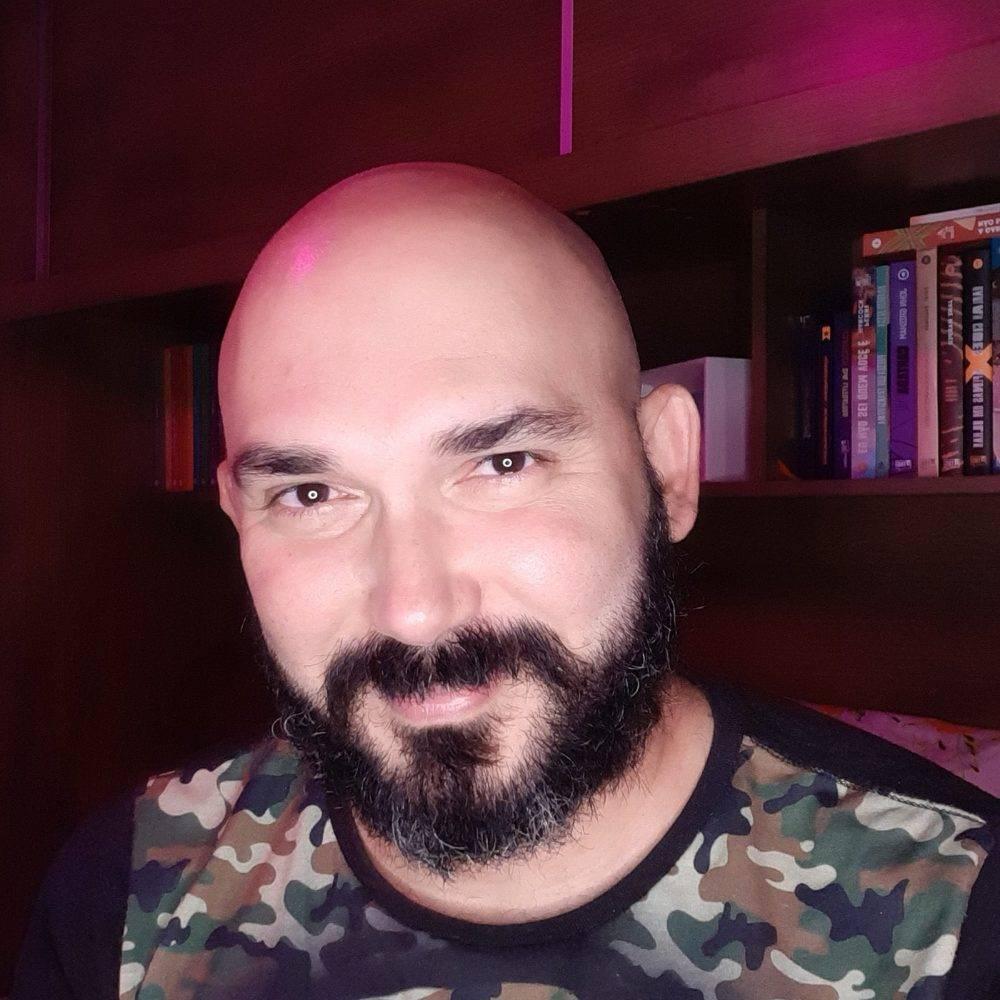 Foto de Flavio Guedes. Ele está sorrindo sem mostrar os dentes. Na foto, ele está careca e tem o bigode ligado à barba que está começando a ficar grisalha, bigode e barba são negros. Ao fundo há uma estante com livros iluminada por uma luz rosa.