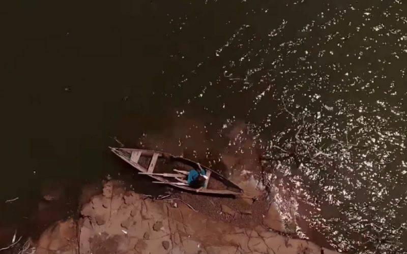 Cena do filme O Pescador e o Rio. Imagem vista de cima. Mostra uma mulher com um vestido azul sentada em uma canoa nas margens de um rio.