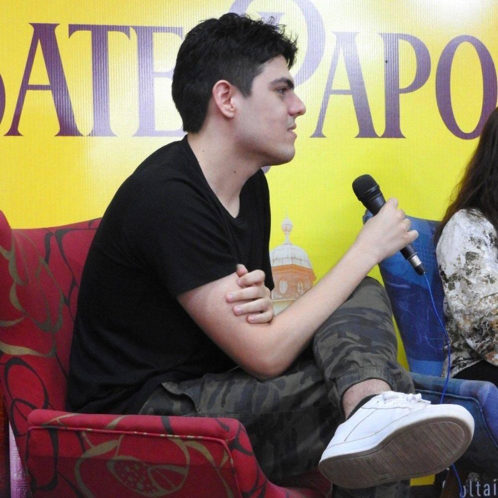Foto de Carlos César, autor de A Sociedade do Através. Ele veste uma camisa preta, calça com estampa militar e tênis branco. Ele segura um microfone e está sentado em uma cadeira acolchoada vermelha.