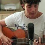 Foto de Tauana Queiroz. Com um violão nas mãos e um microfone em um tripé na frente, Tauana olha para baixo enquanto dedilha as cordas do violão. Veste uma camisa branca.