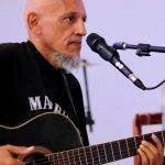 Foto de James Brito. Ele está tocando um violão e tem um microfone em um tripé na frente dele. Ele está de lado, tem uma barba branca apenas no queixo e traz a cabeça raspada. Veste uma camisa preta.